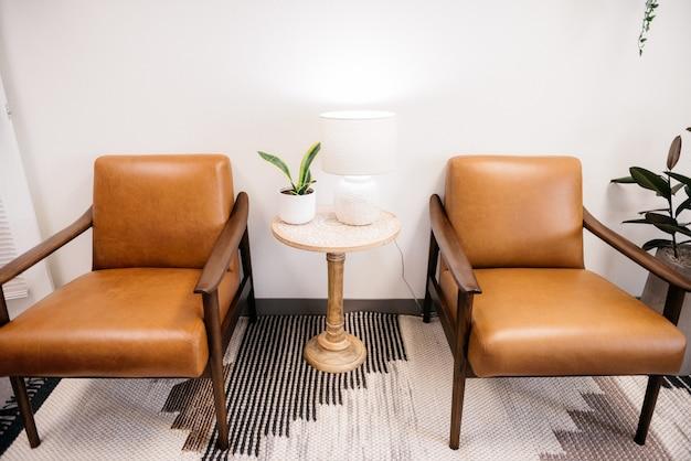 Foto de ângulo alto de cadeiras marrons com lâmpada branca e uma planta de casa em uma mesa na sala de estar