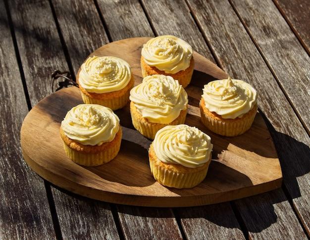 Foto de ângulo alto de deliciosos cupcakes de creme de manteiga doce em uma superfície de madeira