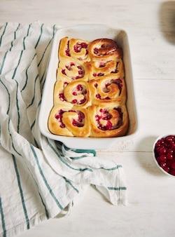 Foto de ângulo alto de deliciosos pastéis de caracol de groselha em uma forma sobre uma mesa de madeira