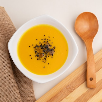 Foto de ângulo alto de sopa de abóbora com gergelim ao lado de uma grande colher de pau em uma mesa branca