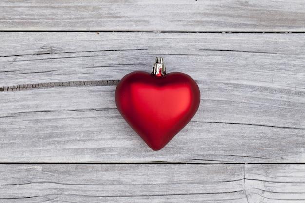 Foto de ângulo alto de um enfeite de natal vermelho em forma de coração em uma superfície de madeira