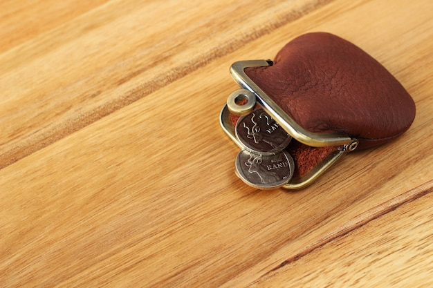 Foto de ângulo alto de uma bolsa de couro e algumas moedas em uma superfície de madeira