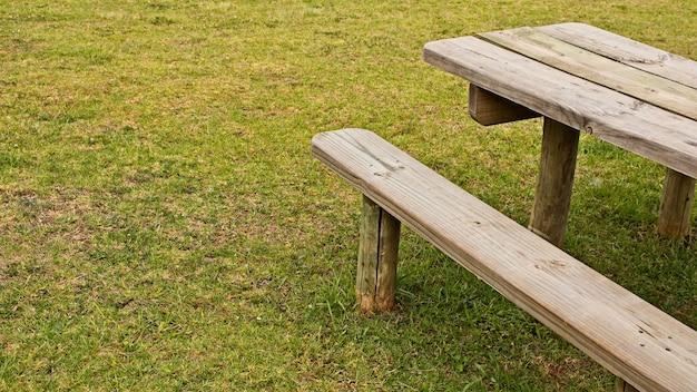 Foto de ângulo alto de uma mesa de madeira e um banco no campo coberto de grama