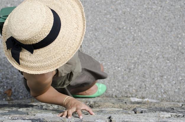 Foto de ângulo alto de uma mulher com chapéu de palha e sapatos verdes encostado na parede