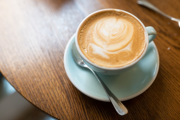 Foto de ângulo alto de uma xícara de cappuccino em uma superfície de madeira