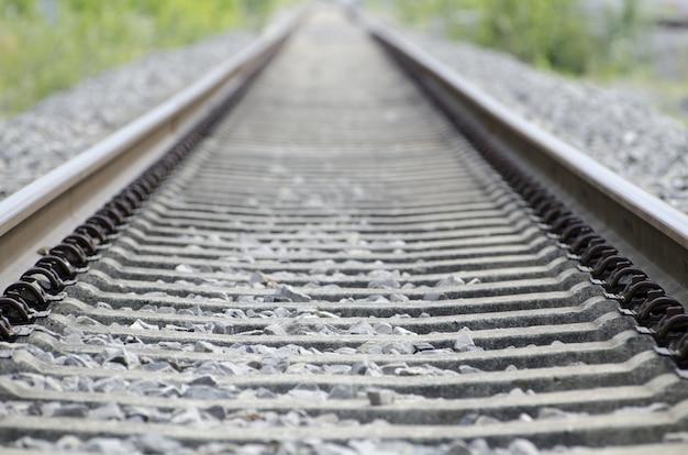 Foto de ângulo alto dos trilhos ferroviários antigos e enferrujados, cobertos por pequenas pedras