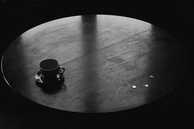 Foto de ângulo alto em tons de cinza de uma xícara de chá de cerâmica preta em uma mesa redonda de madeira