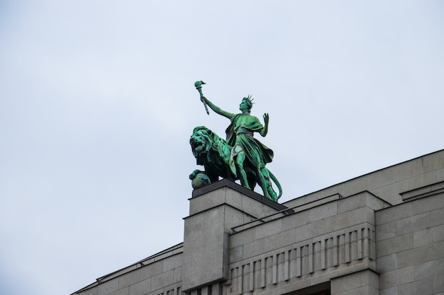 Foto de ângulo baixo da estátua do leão no banco nacional da república tcheca sob um céu nublado