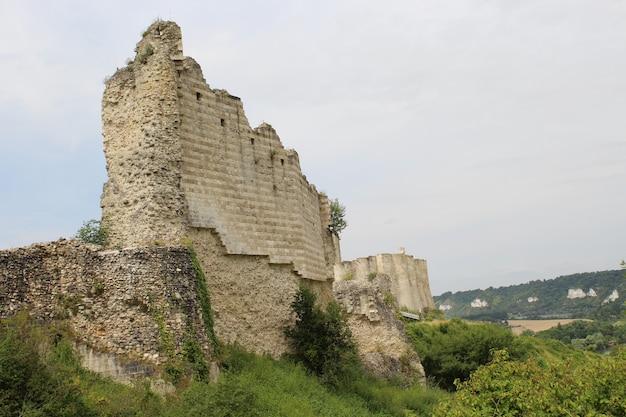 Foto de ângulo baixo das ruínas de um castelo na frança com o céu cinza ao fundo