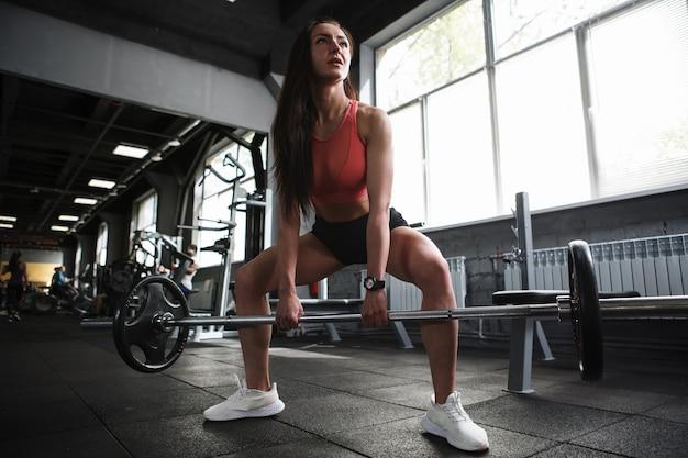 Foto de ângulo baixo de uma mulher fitness fazendo agachamentos de sumô com barra