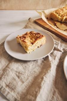 Foto de ângulo superior de um pedaço do delicioso bolo de folha de jerry crumble em uma mesa de madeira branca