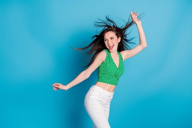 Foto de animado energético menina dança discoteca ar vento golpe cabelo levantar mãos vestir calças de regata isoladas sobre fundo de cor azul
