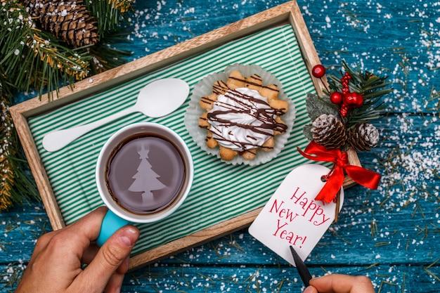 Foto de ano novo de chá com imagem de abeto, bolo na mesa com ramo de abeto, pessoa escrevendo desejos no cartão postal