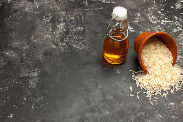 Foto de arroz cru de vista frontal com óleo na superfície cinza óleo de arroz escuro