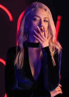 Foto de arte moda de modelo elegante em maiô preto sedutor com holofotes de clube colorido de luz néon