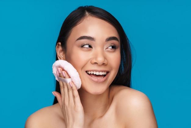 Foto de asiático positivo otimista jovem posando isolado na parede azul, segurando o sopro de pó.