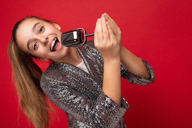 Foto de atraente feliz positiva morena mocinha usando vestido elegante brilho em pé isolado sobre a parede de fundo vermelho, cantando a música para o microfone de prata, olhando para a câmera.