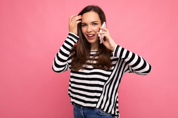 Foto de atraente jovem emocional falando no smartphone, vestindo uma blusa listrada isolada sobre um fundo com espaço de cópia, olhando para a câmera.