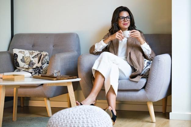 Foto de atraente jovem empresária bebendo chá verde matcha com leite no café.