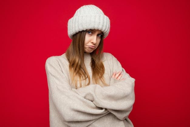 Foto de atraente melancólica jovem loira escura melancólica em pé isolado sobre a parede de fundo vermelho, vestindo um suéter bege quente e um chapéu bege de inverno, olhando para a câmera.