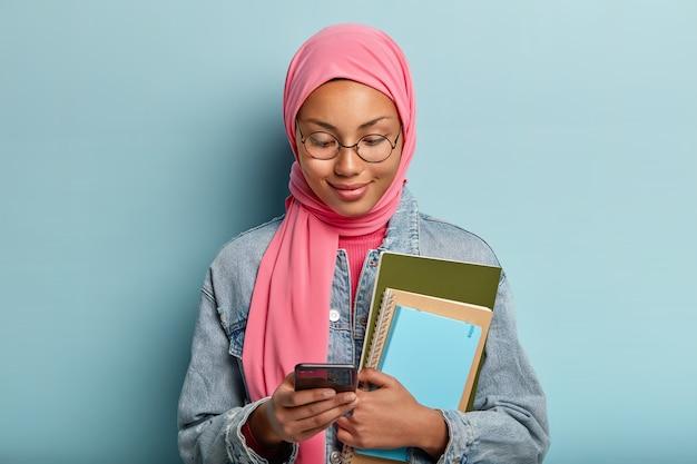 Foto de atraente mulher árabe mestiça focada no celular, trabalha com arquivos no celular, gosta do novo aplicativo, segura caderno espiral, vestida com jaqueta jeans e hijab rosa de acordo com a religião.