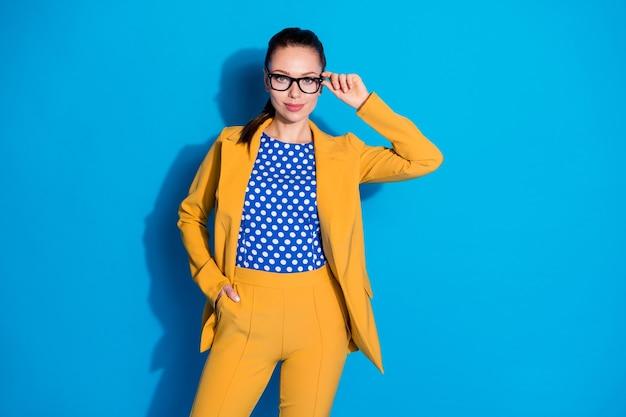 Foto de atraente mulher de negócios bem-sucedida trabalhador segurar mão tocar óculos boa visão usar blazer amarelo terno camisa de blusa pontilhada isolado fundo de cor azul