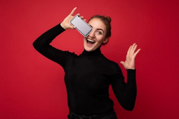 Foto de atraente positiva jovem morena vestindo suéter preto em pé isolado sobre um fundo vermelho, mostrando o telefone móvel com tela vazia para maquete, olhando para a câmera.