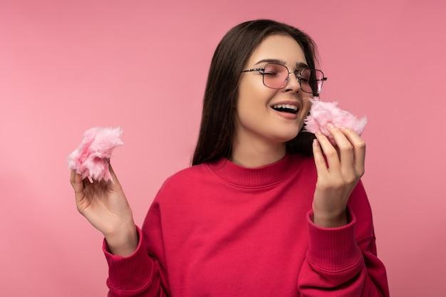 Foto de atraente senhora de óculos joga com algodão doce doce se diverte feliz usar suéter rosa casual isolado fundo de cor rosa.
