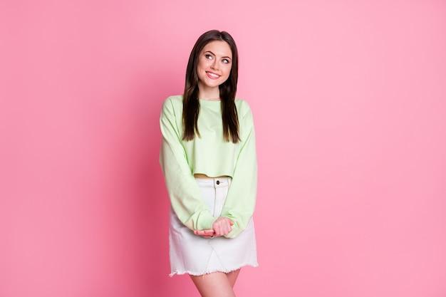 Foto de atraente senhora engraçada interessada olhar maravilhado lado vazio espaço vazio pessoa tímida usar mini saia jeans casual verde coletor com fundo de cor pastel rosa