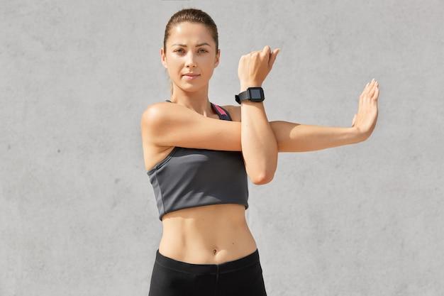 Foto de auto-confiante feminino estica as mãos, aquece antes do treino, tem corpo desportivo, usa smartwatch