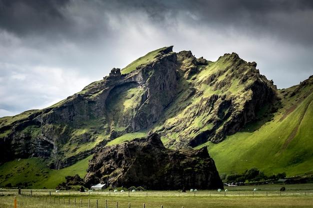 Foto de baixo ângulo das magníficas montanhas cobertas de grama capturada em um dia nublado