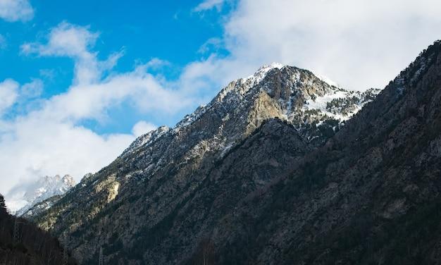 Foto de baixo ângulo de altas montanhas rochosas sob um céu nublado