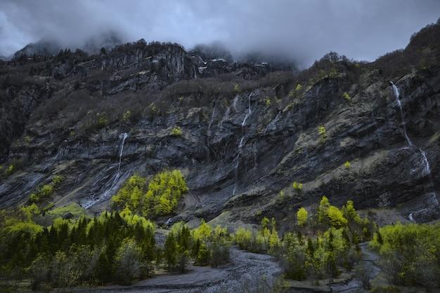 Foto de baixo ângulo de cachoeiras em uma montanha rochosa
