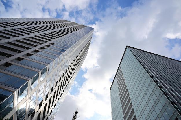 Foto de baixo ângulo de modernos arranha-céus de vidro contra o céu nublado