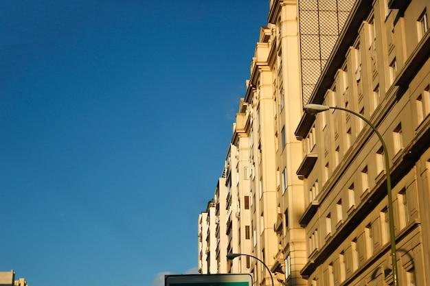 Foto de baixo ângulo de postes de luz e prédios residenciais sob um céu azul