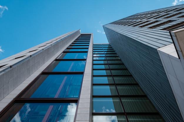 Foto de baixo ângulo de um arranha-céu moderno com janelas de vidro e céu azul