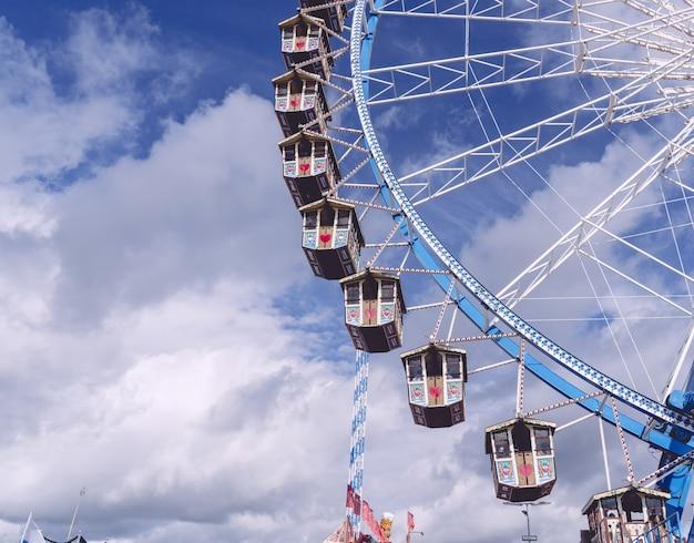 Foto de baixo ângulo de um carrossel circular girando sob um céu cheio de nuvens