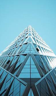 Foto de baixo ângulo de um edifício moderno de vidro no fundo do céu azul