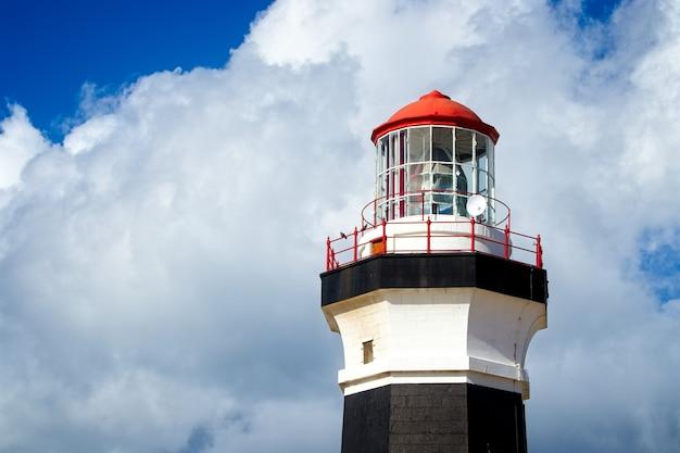 Foto de baixo ângulo de um farol sob a bela nuvem no céu