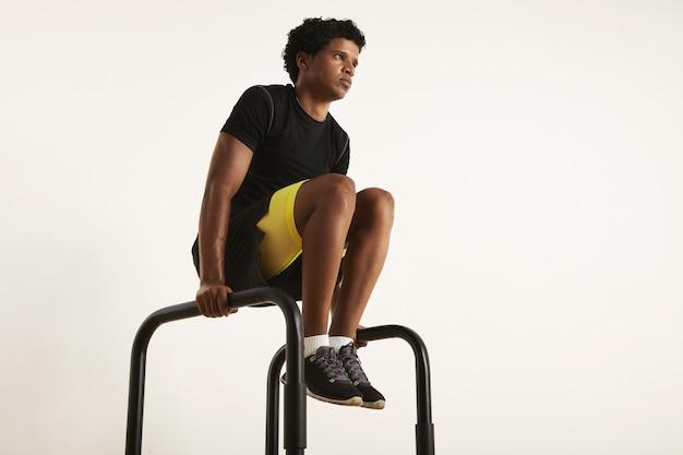 Foto de baixo ângulo de um modelo masculino preto magro e musculoso forte com um afro em roupas de treino pretas, levantando os joelhos em barras paralelas isoladas em branco.