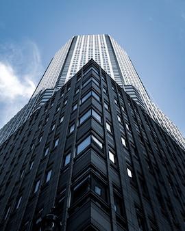 Foto de baixo ângulo de um prédio alto com um céu azul ao fundo em nova york