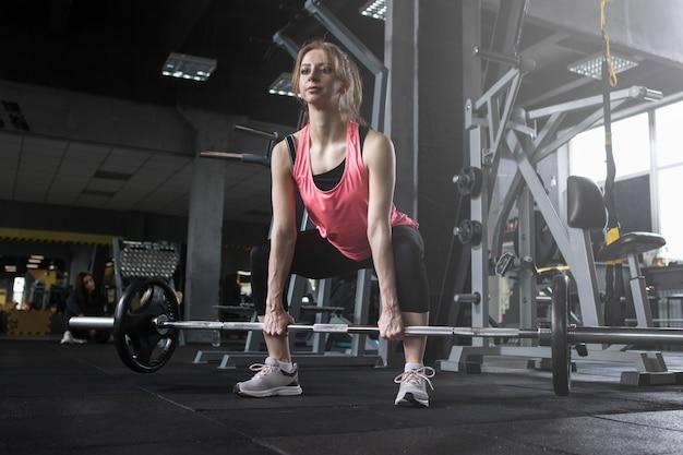 Foto de baixo ângulo de uma atleta feminina focada levantando barra na academia