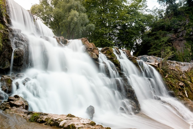 Foto de baixo ângulo de uma cachoeira rochosa com árvores verdes ao fundo