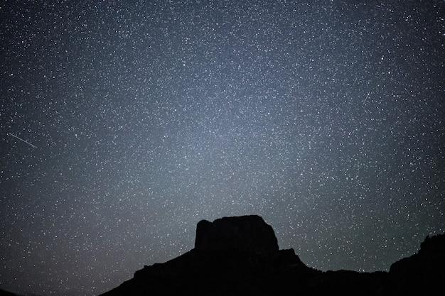 Foto de baixo ângulo de uma colina sob um lindo céu estrelado