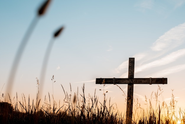 Foto de baixo ângulo de uma cruz de madeira feita à mão em um campo gramado com um lindo céu