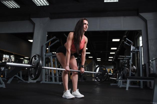 Foto de baixo ângulo de uma fisiculturista fazendo exercícios de levantamento terra na academia