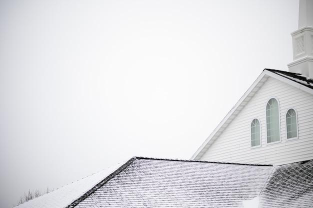 Foto de baixo ângulo de uma igreja com um grampo sob o céu claro