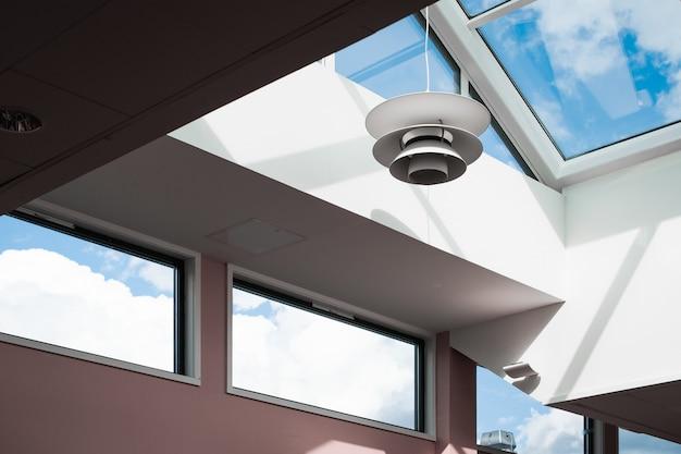 Foto de baixo ângulo de uma lâmpada pendurada dentro de um prédio com teto de vidro