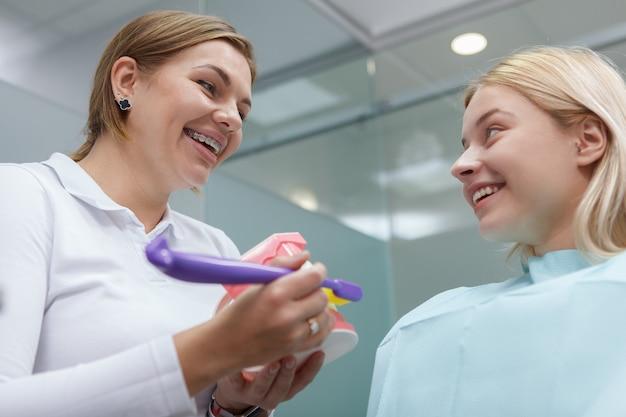 Foto de baixo ângulo de uma mulher alegre conversando com seu dentista após um exame dentário