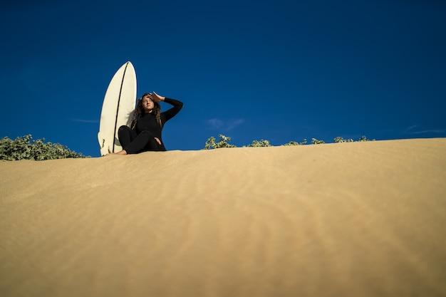 Foto de baixo ângulo de uma mulher atraente sentada em uma colina arenosa com uma prancha de surfe ao lado